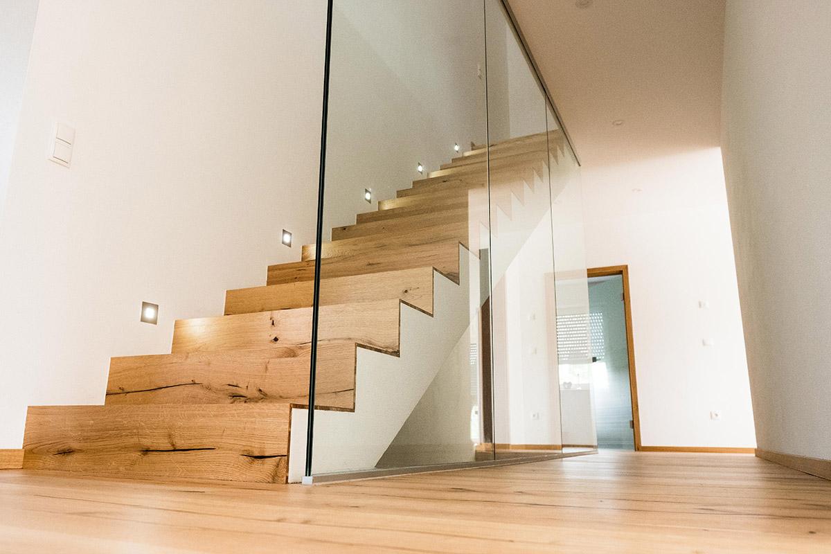 Holztreppe mit Glas in einem Einfamilienhaus